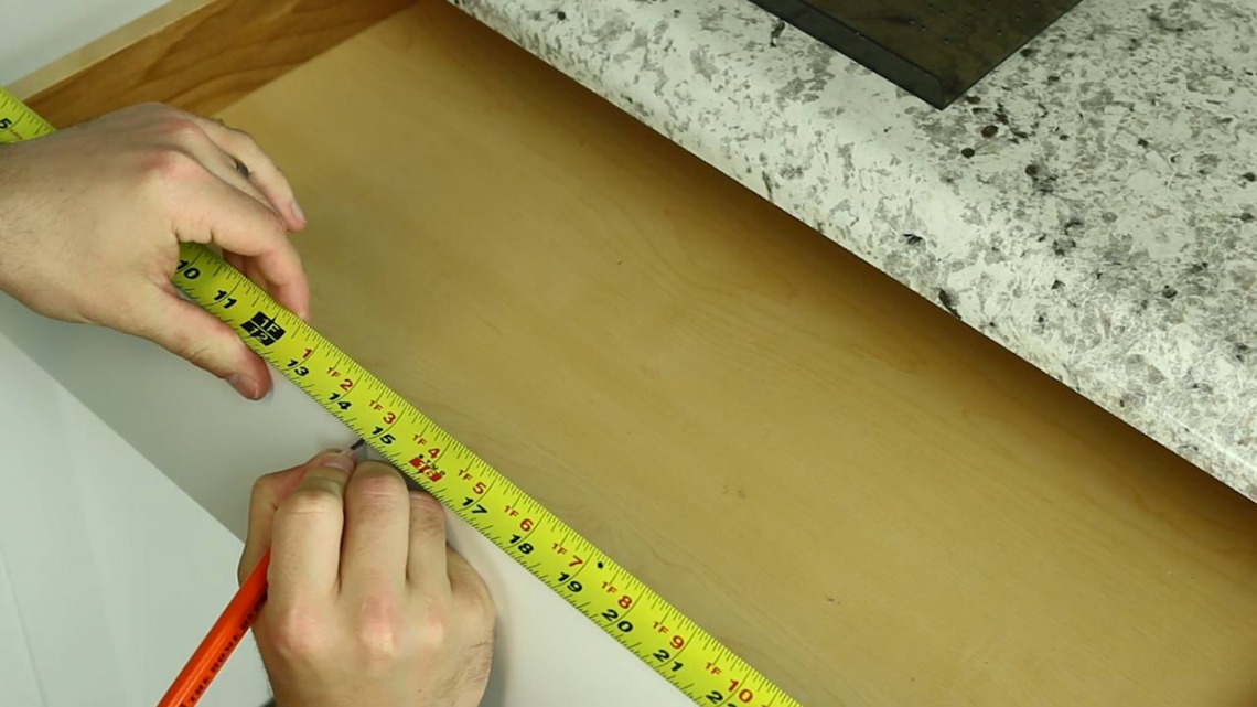 Step 5: Use measuring tape to accurately measure the drawer's center point. | Cabinet Hardware Installation